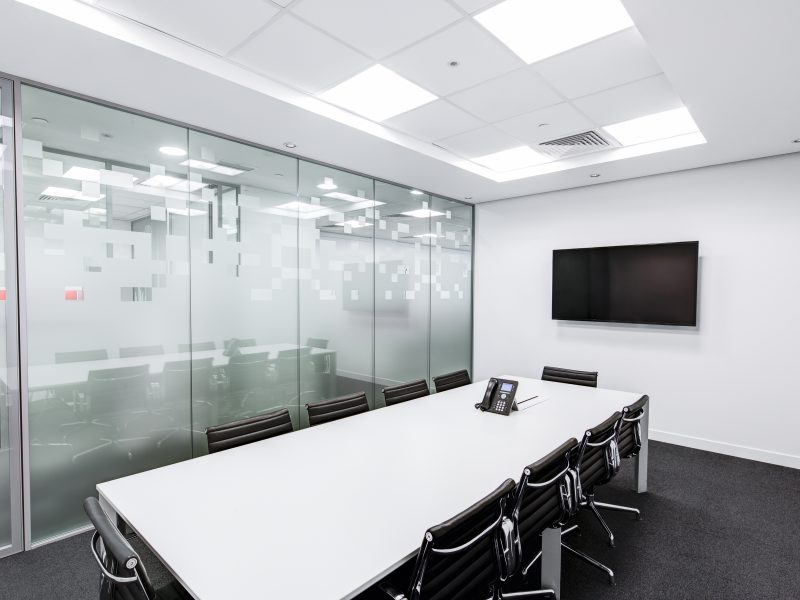 Offices conference room with white desk and monitor on the wall